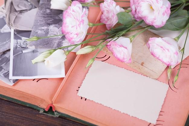 Old photo album, photos, camera, tender pink flowers on a dark wooden background. Premium Photo