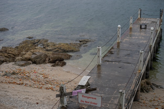 The old pier is beside the quiet sea. it is dangerous place to entry. Premium Photo