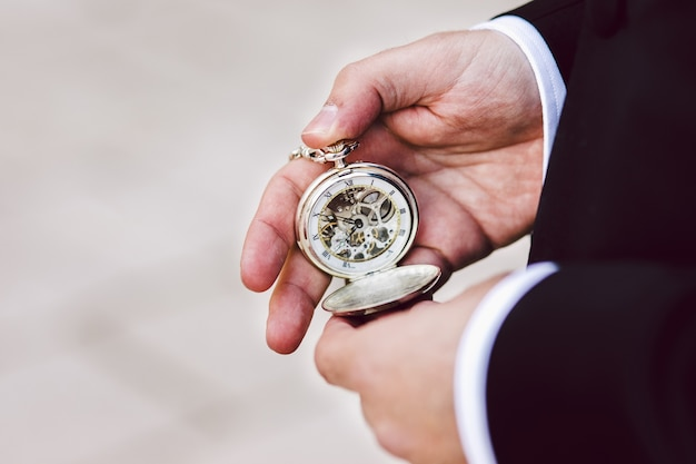 Old pocket watch in the hands of a man Premium Photo