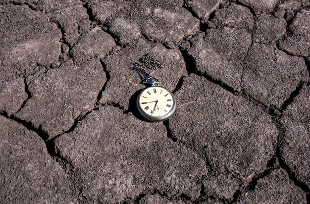 마른 땅에 오래 된 회중 시계 프리미엄 사진