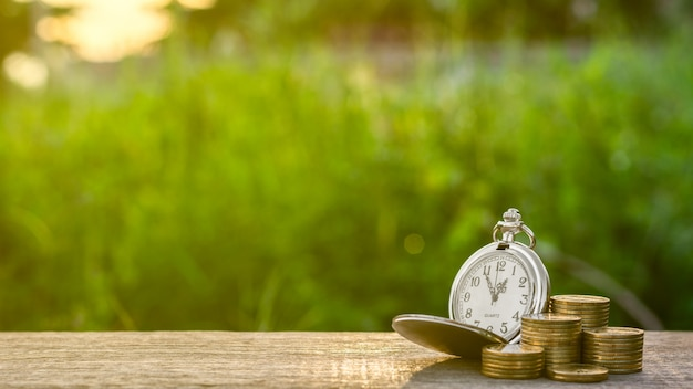 Old pocket watch and a stack of golden coins Premium Photo