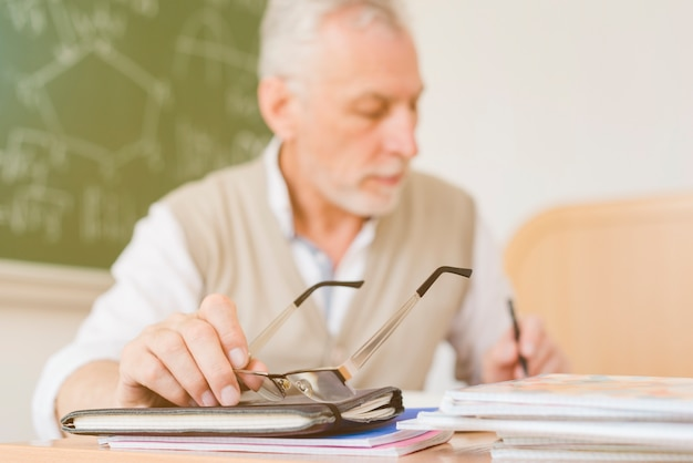 Old professor making notes in copybook Free Photo