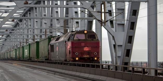 Старый красный поезд с зелеными вагонами в дневное время Бесплатные Фотографии
