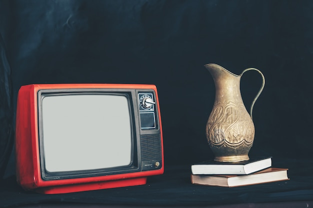 Old retro tv by placing flower vases on books Free Photo