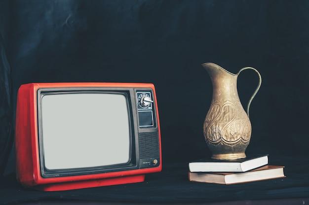 Старый ретро-телевизор, поместив вазы с цветами на книги Бесплатные Фотографии