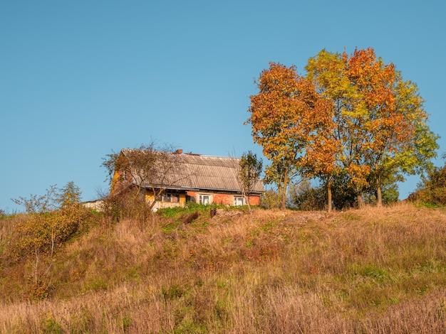 가 언덕에 오래 된 시골 집입니다. 전원 생활. 프리미엄 사진