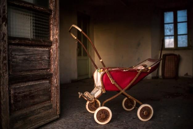 Старая ржавая детская коляска внутри здания с обветренными дверями и окнами Бесплатные Фотографии