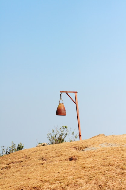 Old rusty bell with dry grassland and wild with blue sky on the valley mountain at doi pha tang hill in thailand Premium Photo