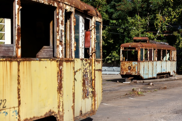 Old rusty destroyed tram wagons outdoors at sunny day. Premium Photo