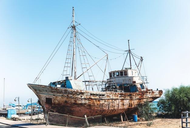 Old rusty fishing ship standing on land near sea. Premium Photo