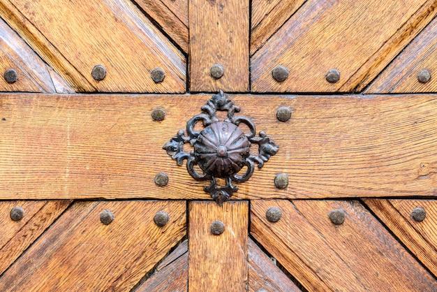 Old rusty gate handle on wooden door. Premium Photo