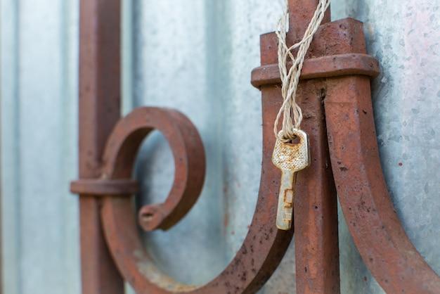 古いさびたキーが古いフェンスにぶら下がっています。失われた鍵と機会の概念。テキストのコピースペースでクローズアップ。 Premium写真