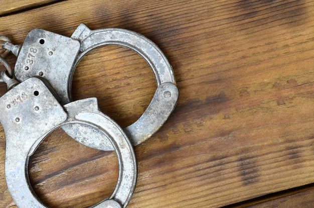 Old and rusty police handcuffs lie on a scratched wooden surface. Premium Photo