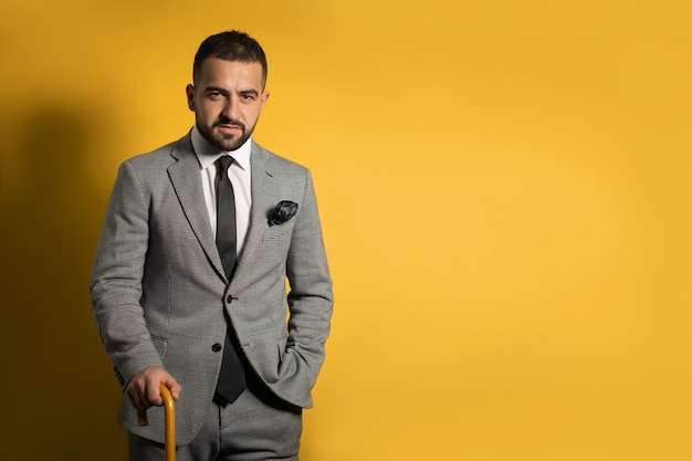Олдскульный модный стильный красивый молодой человек в сером костюме с поднятой рукой, стоя с тростью или зонтиком в руке, изолированной на желтой стене Premium Фотографии