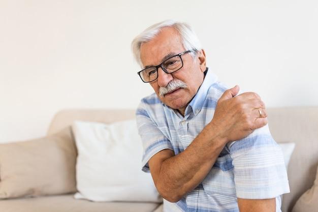 Старый старший мужчина с болью в плече Premium Фотографии