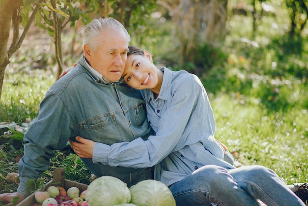 Old senior standing in a summer garden with harvest Free Photo