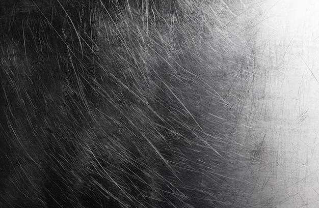 古い光沢のある金属の背景、傷を持つ暗いブラシをかけられた金属のテクスチャ Premium写真