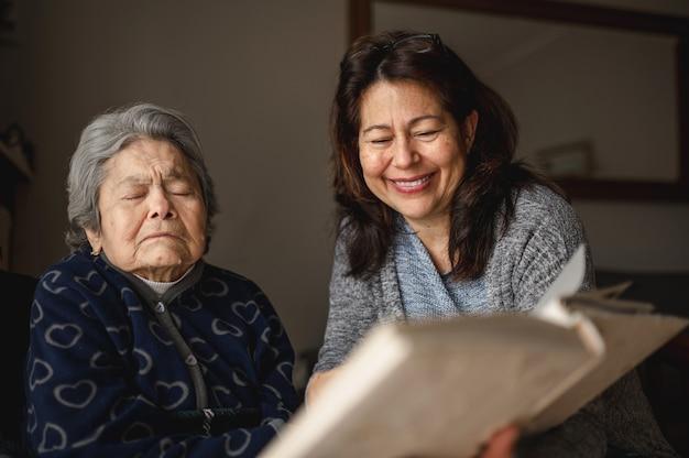 Старая больная женщина с потерей памяти. улыбающаяся дочь показывает фотоальбом. Premium Фотографии