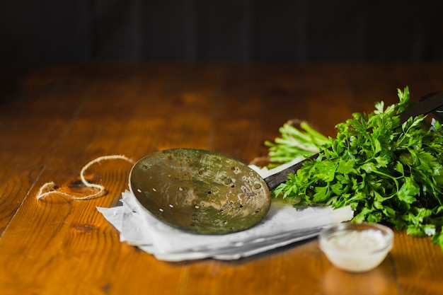 An old skimmer on tissue paper with coriander and garlic dip bowl over the wooden table Free Photo