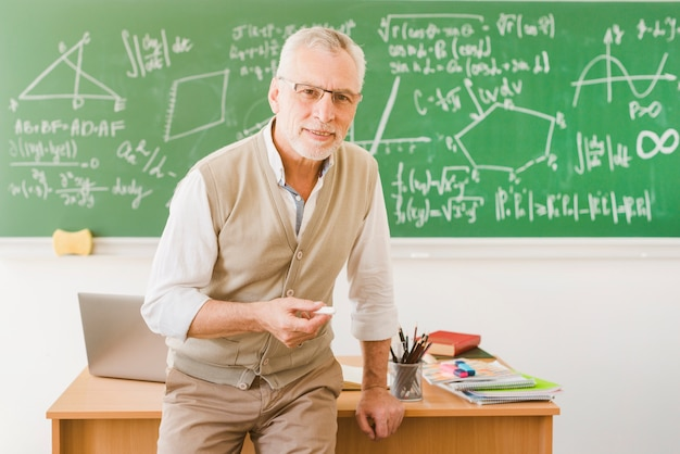 Old smiling teacher with chalk in classroom Free Photo