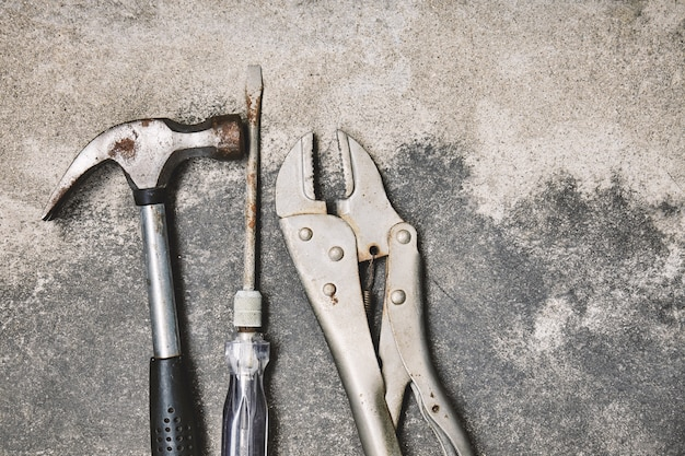 Old steel oxided working tools, hammer, screwdriver and wrench on cement background Premium Photo