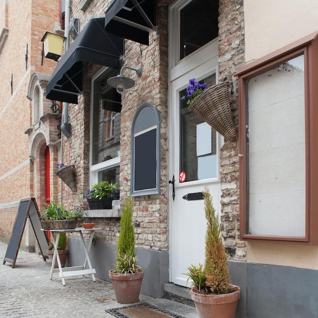 ベルギー、ブルージュの古い通りのカフェ花 Premium写真