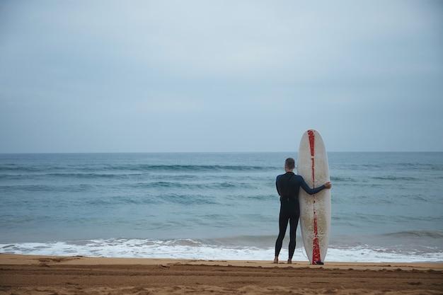 ロングボードを持った古いサーファーは、海の前のビーチに一人で滞在し、サーフィンに行く前に海の波を見て、早朝にフルウェットスーツを着ています 無料写真