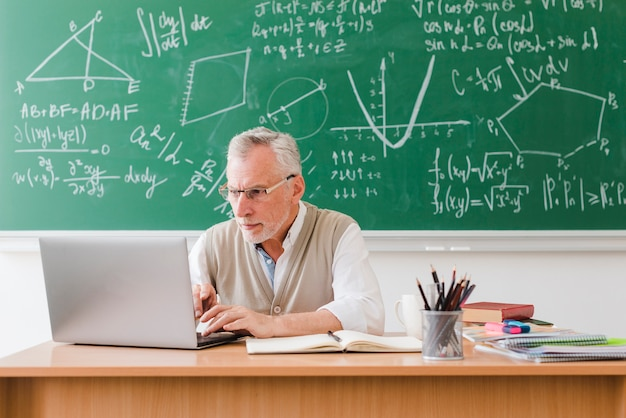 Old teacher using laptop in classroom Free Photo