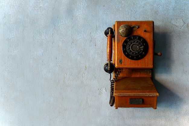 Old telephone on brick wall with over light in the