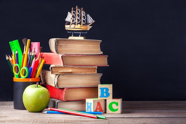 Old textbooks and school supplies are on the rustic wooden table on a background of black chalk board. Premium Photo