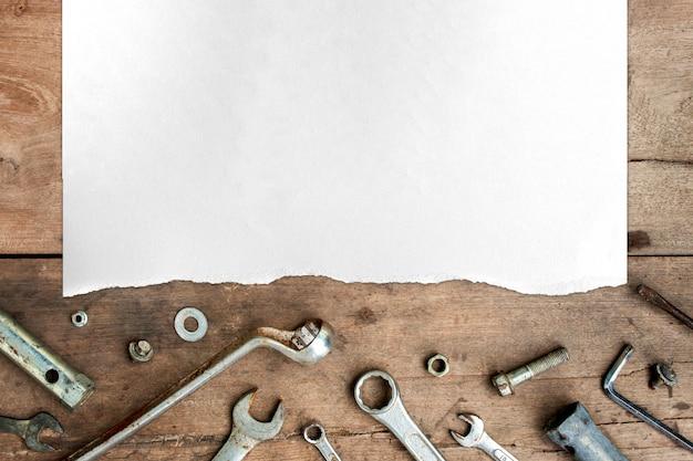 Старые инструменты и белая бумага на фоне деревянного пола Premium Фотографии