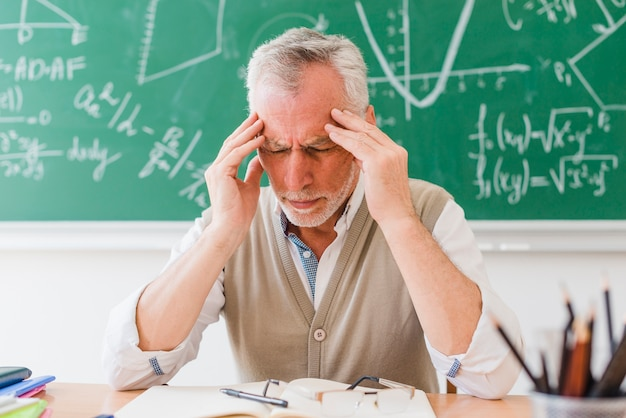 Old tutor with headache in lecture room Free Photo