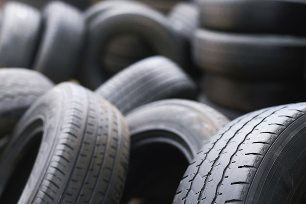 Old used tires stacked with high piles. close up damaged worn black tire tread car. Premium Photo