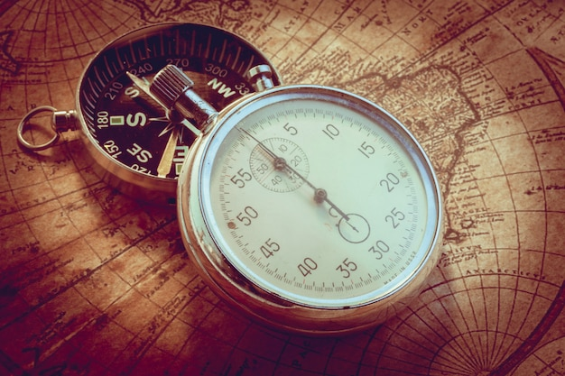 Old vintage compass and travel instruments on ancient map Premium Photo