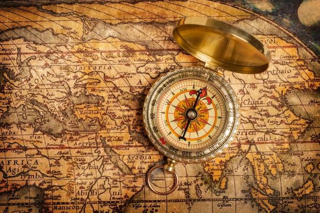 Старый старинный золотой компас на древней карте Premium Фотографии