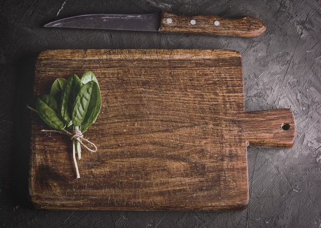 Old vintage kitchen cutting board and bunch with green sorrel leaves, top view Premium Photo