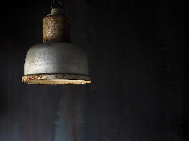 Old vintage metal ceiling lamp hanging in dark room Premium Photo
