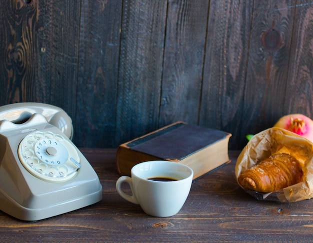 Old vintage telephone coffee book on a wooden background Premium Photo