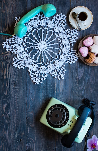 Old vintage telephone with biscotti coffee donuts on a wooden background Premium Photo