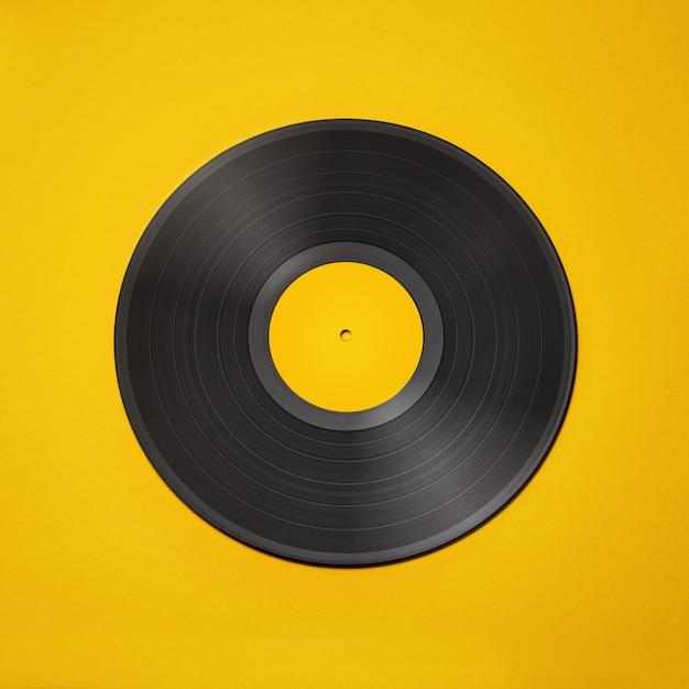 Old vintage vinyl record isolated on yellow background Premium Photo