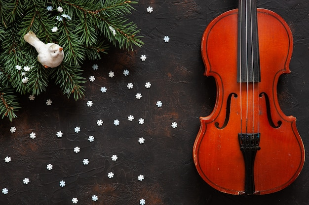 Old violin and fir-tree branches with christmas decor. Premium Photo