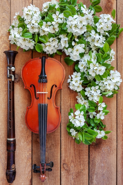 Old violin, flute and blossoming apple tree branches  Photo