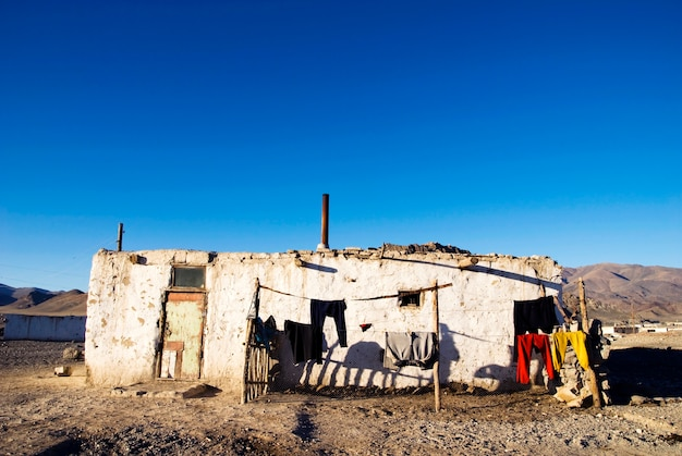 Old weathered house with mountain range in the background Free Photo