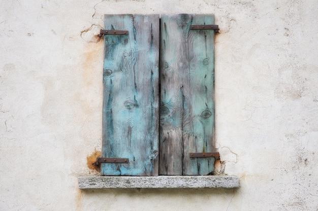青いさびた木製シャッター付きの古い風化した壁 無料写真