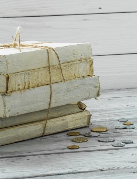 木製の壁にお金とコインの古い白い本 無料写真