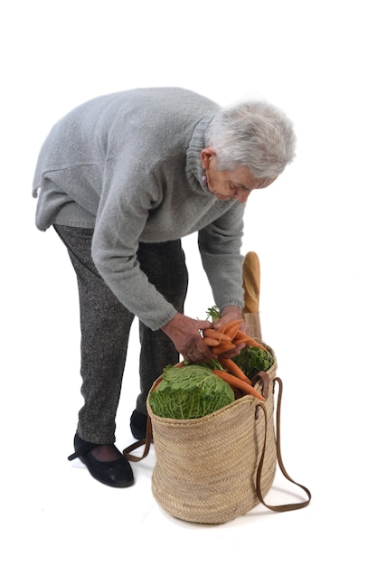 old woman going to buy with a wicker basket isolated on white photo