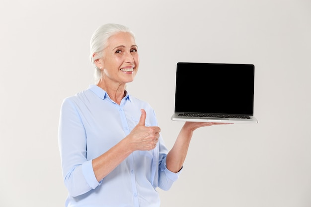Old woman holding laptop and showing thumb up isolated Free Photo