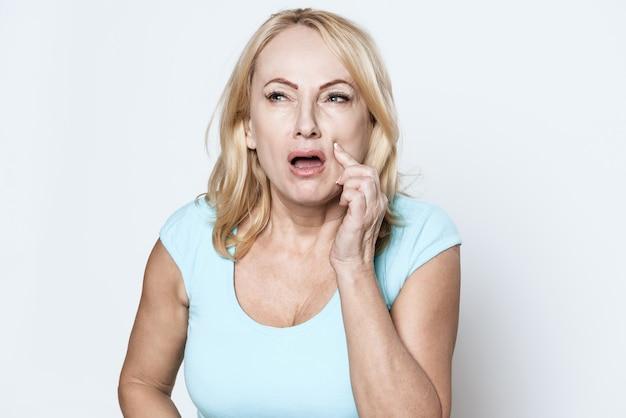 歳の女性が彼女の頬に彼女の手を握っています。 Premium写真