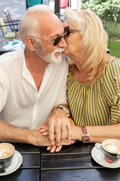 Old woman kissing her husband on the cheek Free Photo