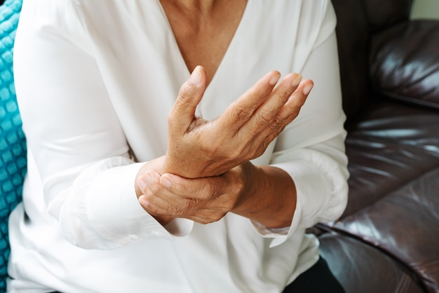 Old woman suffering from wrist hand pain, health problem concept Premium Photo